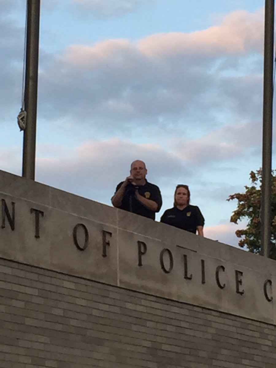 Bridgeport police officers record peaceful protesters from a rooftop