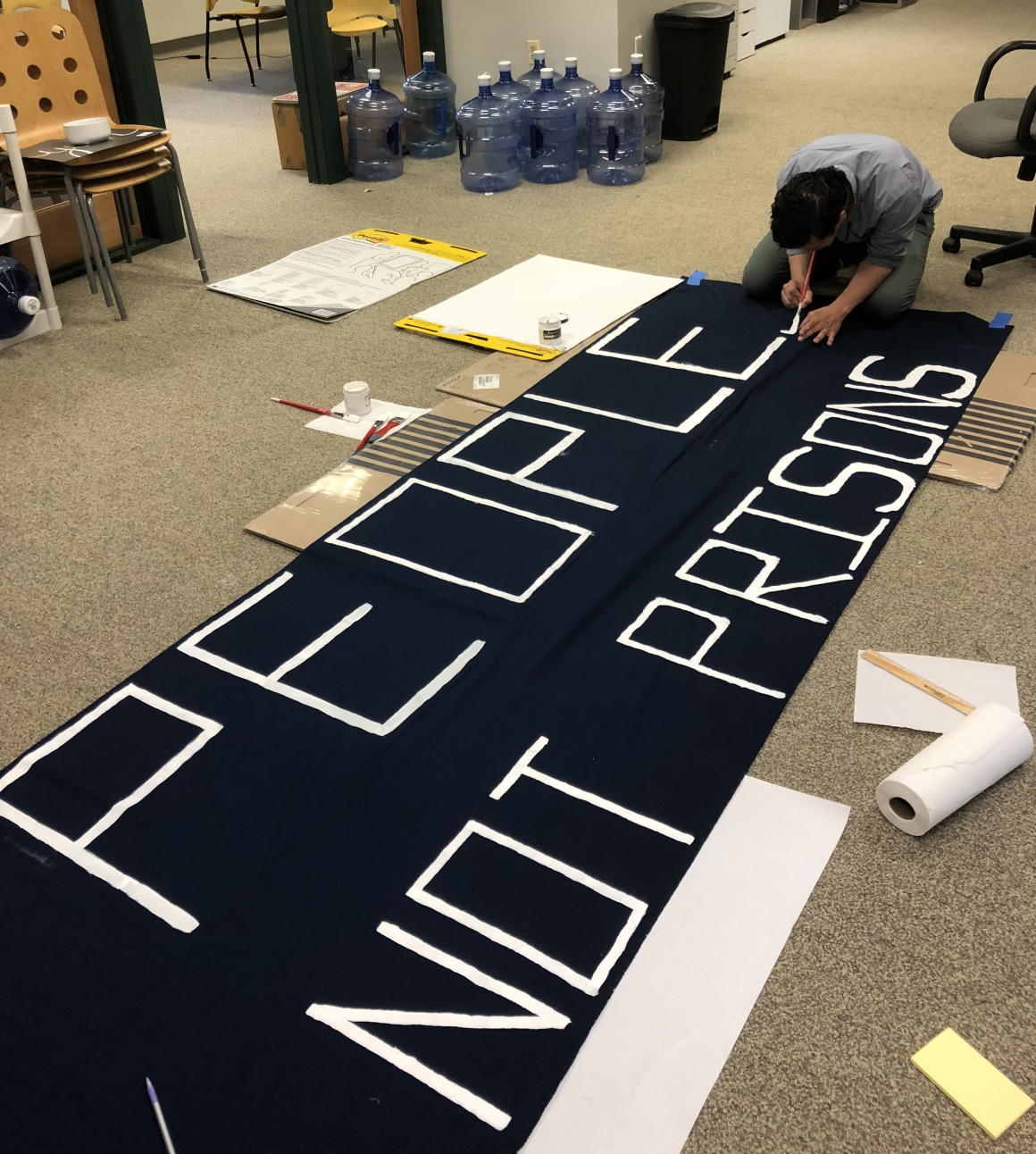"ACLU-CT staff member crouches with a paint brush over a banner that says ""People Not Prisons"""