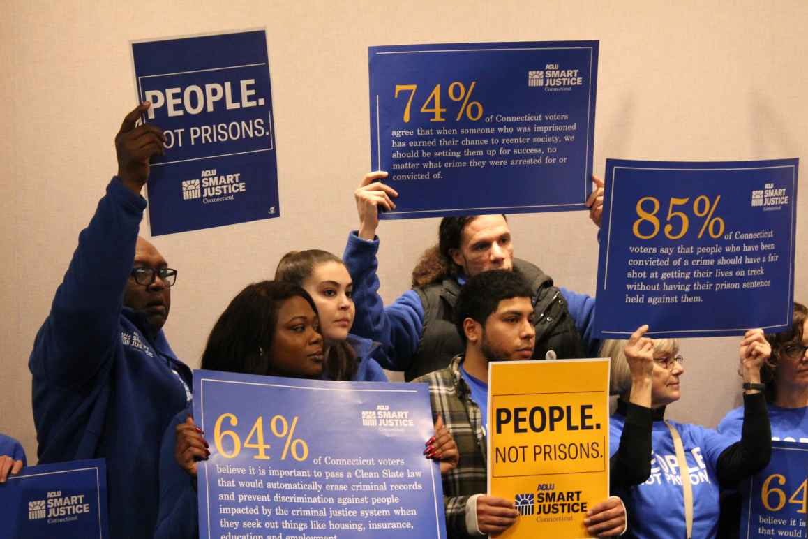 """ACLU-CT Smart Justice leaders stand with """"people not prisons"""" posters at a Connecticut Clean Slate pres conference"""