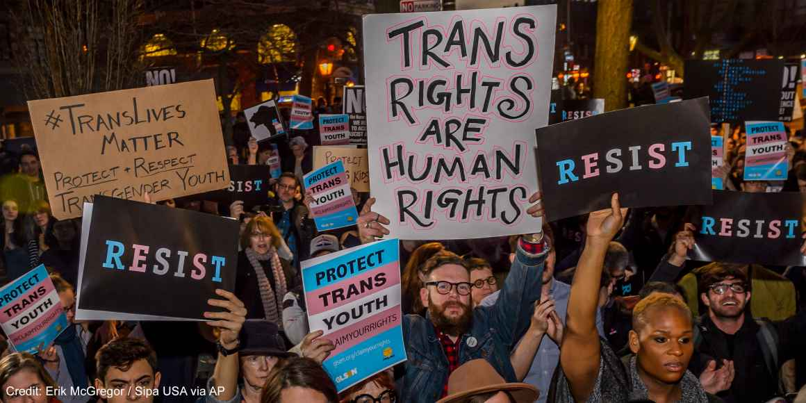 Protestors with signs advocating for the rights of trans youth.