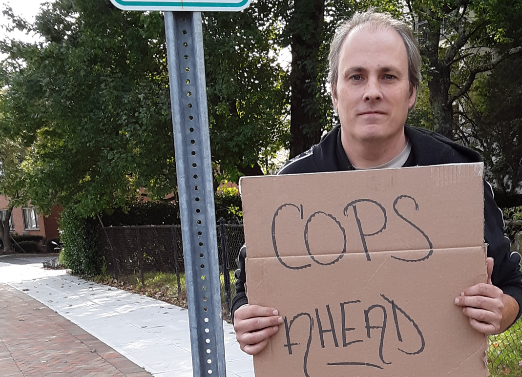 "ACLU of Connecticut client protester Michael Friend holds ""cops ahead"" sign in Stamford"