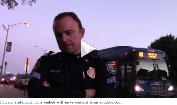 Screen shot of Massimino video. Waterbury police employee can be seen. City bus in the background.