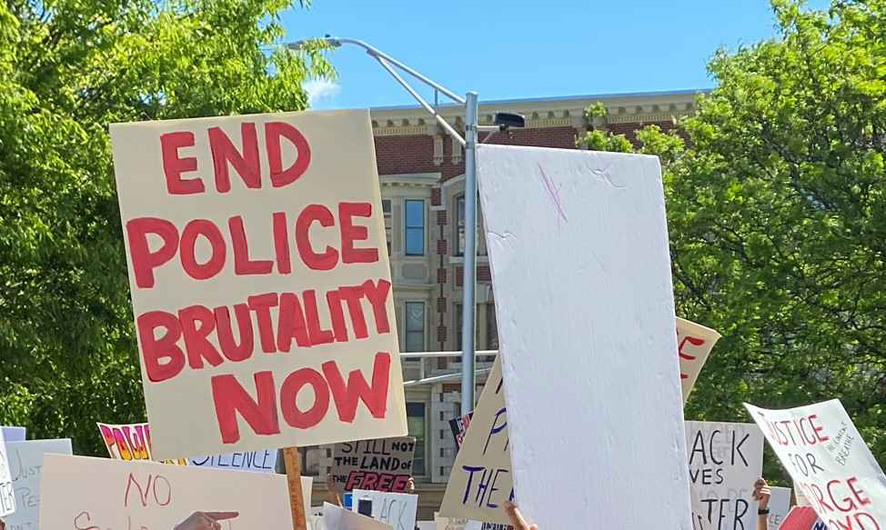 A white sign with red writing, surrounded by other protest signs and against a backdrop of trees. The sign with red writing says: END POLICE BRUTALITY NOW