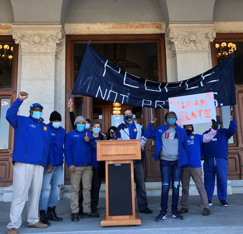 "ACLU-CT Smart Justice leaders stand with ""people not prisons"" banner and ""Clean Slate"" sign outside of the CT State Capitol. They are behind a podium, and wearing blue ""people not prisons"" shirts. Many have fists up in power salutes."
