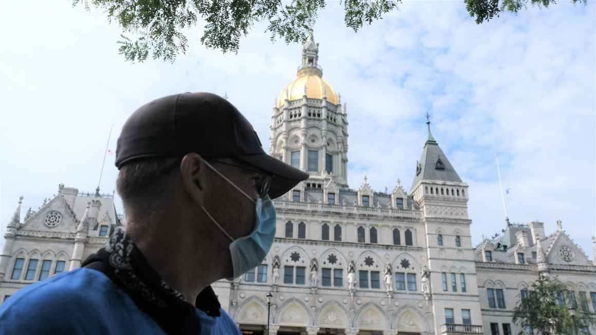 ACLUCT Smart Justice leader Sean Sellars is in the foreground, wearing a mask and baseball hat, looking toward the CT capitol building. In the background is the Connecticut capitol building and a blue sky.