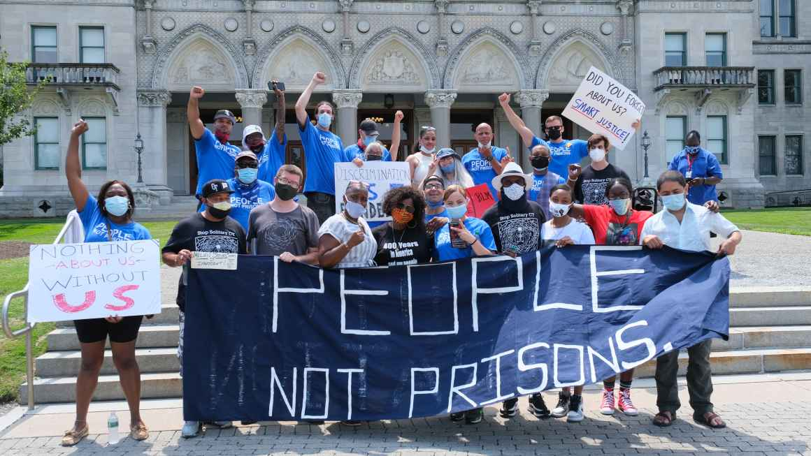 """A group of Smart Justice leaders, advocates, and legislators, all wearing masks, stand behind the ACLU-CT's blue """"People Not Prisons"""" banner outside of the Connecticut state capitol building."""