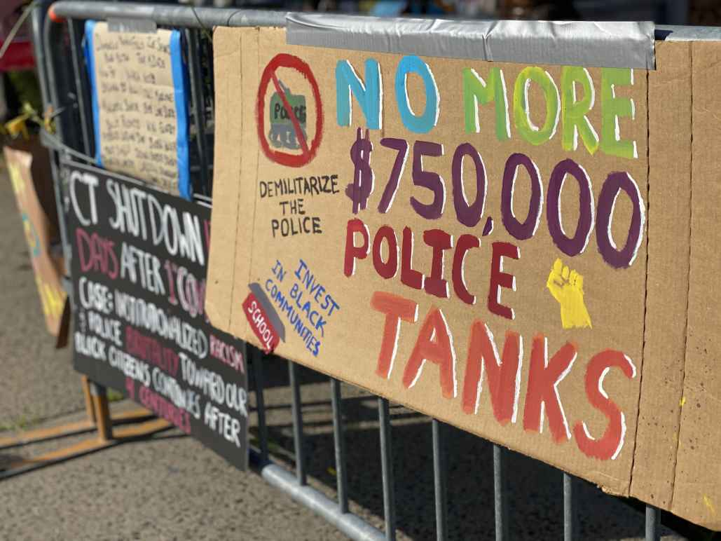 """A cardboard sign taped to a fence outside of a Stamford Connecticut protest. The sign says: """"No more $750,000 police tanks,"""" """"demilitarize the police,"""" and """"invest in our communities."""" It has a drawing of a raised fist, and of a tank crossed out."""