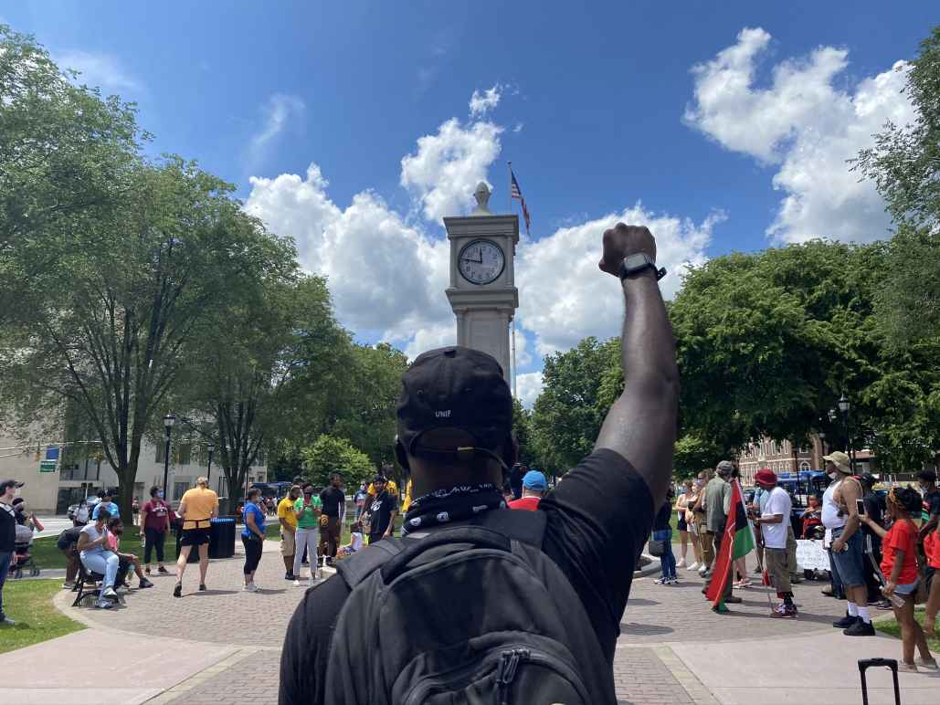A crowd of people is gathered around the clock tower in Waterbury, Connecticut. The sky is blue and it is sunny. A Black man is in the foreground, back to the camera, with fist raised. He is wearing a backpack.