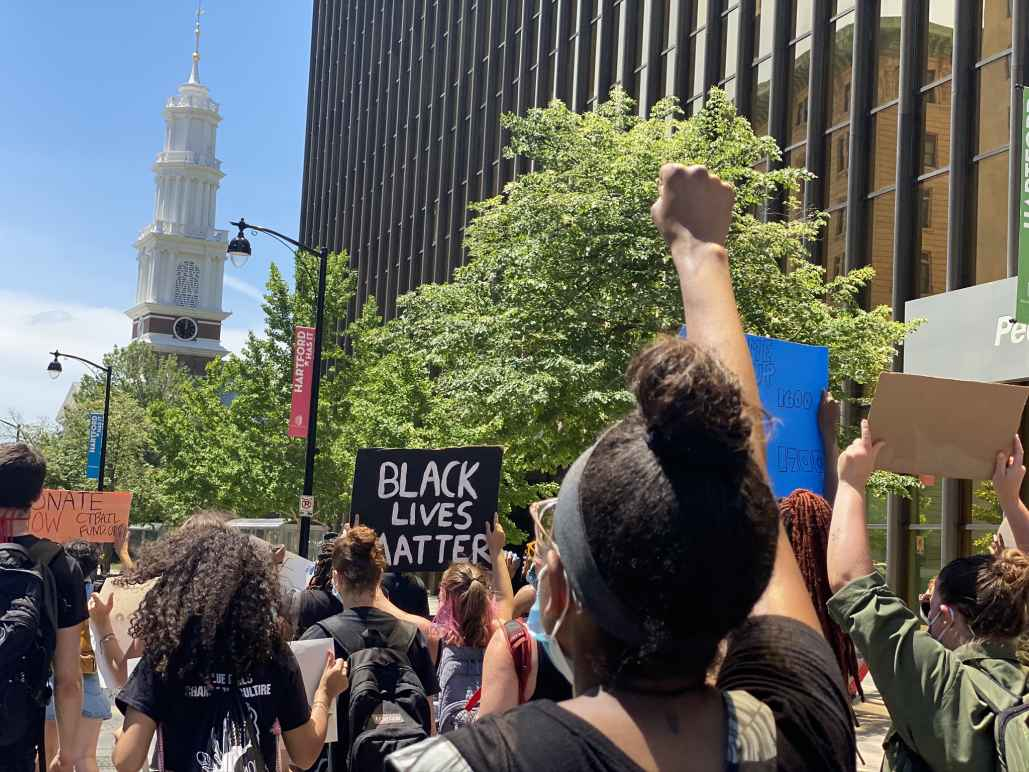 Protesters march in Hartford to call for the state to value Black lives. In the foreground, a person has their fist up. In the background, a Black Lives Matter sign