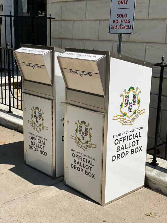"""Two official Connecticut ballot drop boxes sit outside of the Waterbury city hall in 2020. The boxes are large, rectangular, and look like library book drops, with the state of CT seal visible, and """"official ballot drop box,"""" on their fronts and sides"""