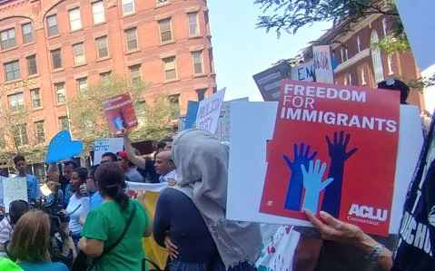 """Photo of crowd at Hartford rally, including red ACLU of Connecticut sign that says """"freedom for immigrants"""""""
