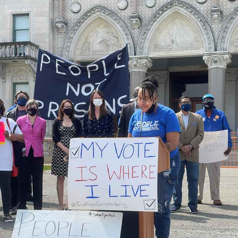 """ACLU-CT public policy and advocacy director Claudine Fox, in a blue """"people not prisons"""" smart justice shirt, speaks behind a podium in front of the CT capitol building. The podium sign says, my vote is where I live."""