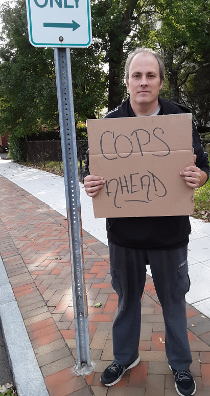 "ACLU of Connecticut lawsuit plaintiff protester Michael Friend holds ""cops ahead"" sign in Stamford"
