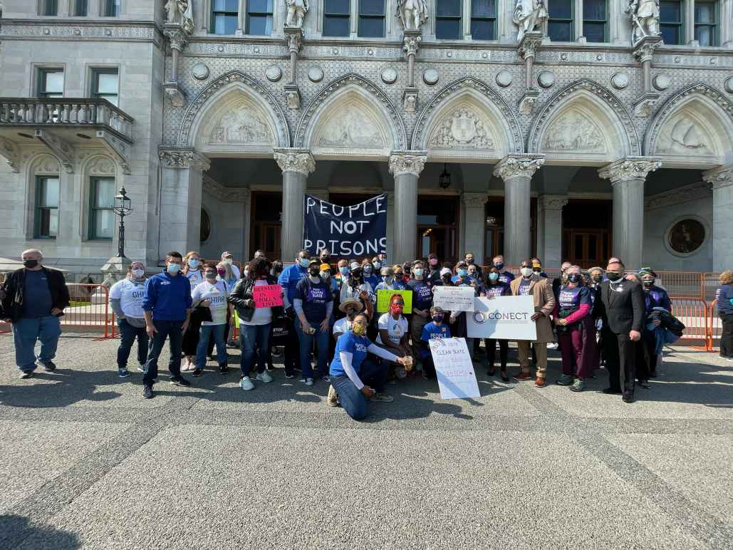 """A group of Smart Justice leaders and activists with CONECT kneel and stand in front of the CT Capitol after a Clean Slate press conference. A blue """"people not prisons"""" banner is in the background."""
