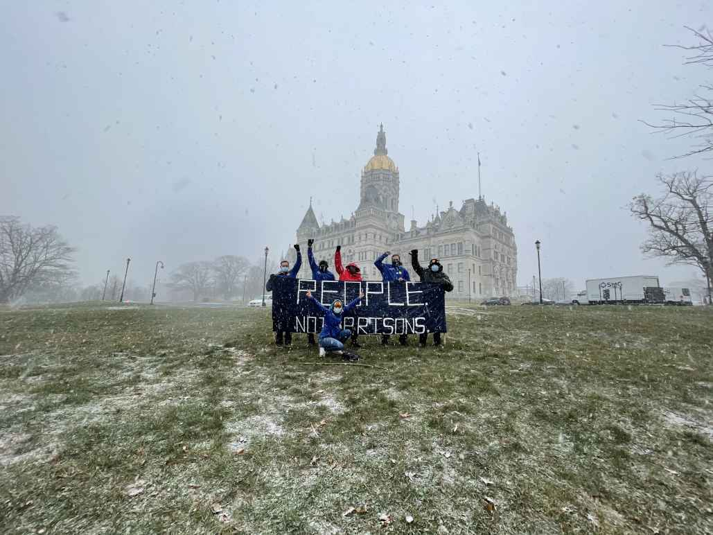 """A photo of the Connecticut State Capitol and ACLU-CT Smart Justice leaders with a blue """"people not prisons banner."""" Foreground: capitol lawn, dusted w snow. Middleground: 6 leaders, fists up, hold the banner. Background: snowy sky and capitol building"""