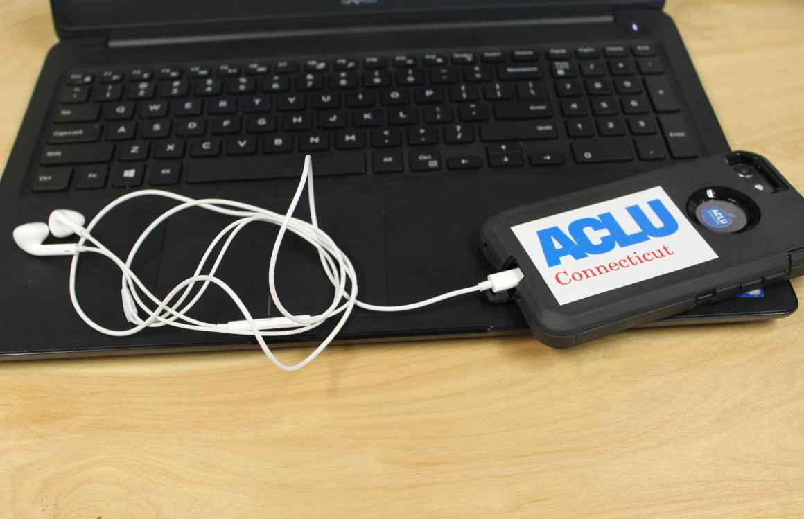 ACLU of Connecticut photo of laptop, phone, headphones with an ACLU of Connecticut sticker
