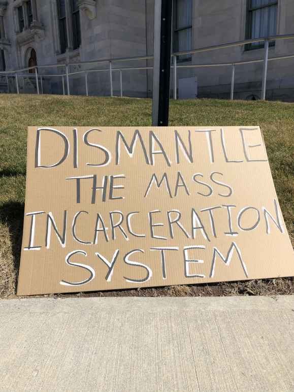 """A cardboard sign sits on the grass in front of the CT state capitol building. In black letters with white background, the sign says: """"dismantle the mass incarceration system"""""""