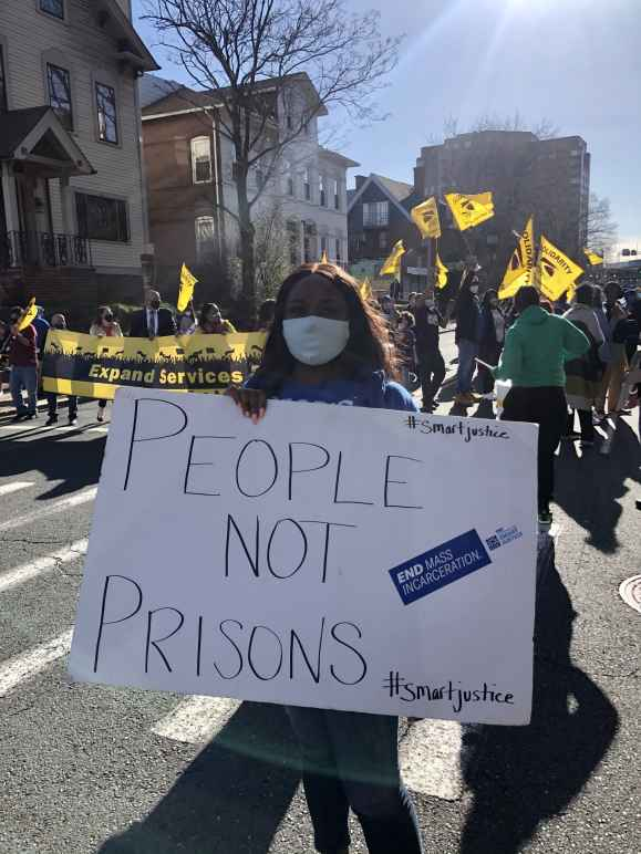 """Smart Justice leader Shelby Henderson holds a white sign that says """"PEOPLE NOT PRISONS"""" in blue ink. Behind her is a crowd waving yellow flags and carrying a banner. They are on a street in Hartford, marching."""