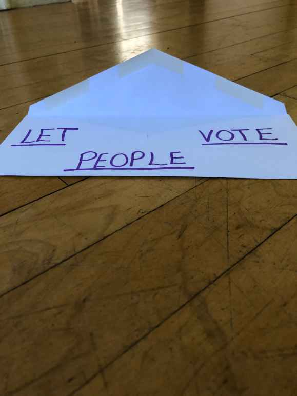 a white envelope against wood background. written on the envelope: LET PEOPLE VOTE