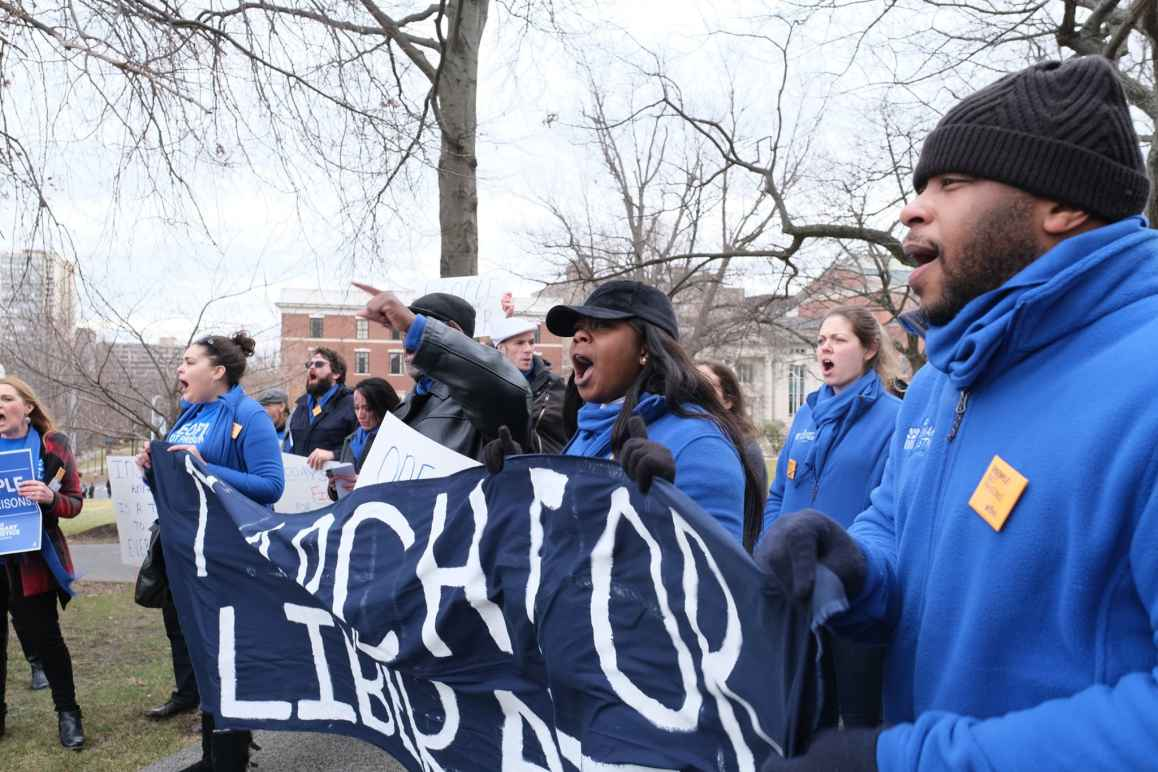 """ACLU-CT Smart Justice leaders, in blue fleeces, stand side by side holding a """"March for Liberation"""" banner. They are joining a chant."""