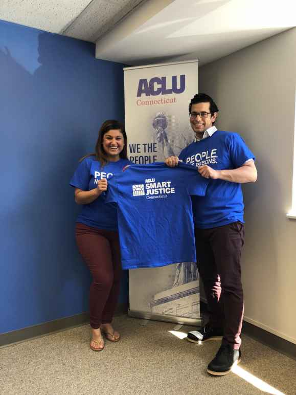 """Melvin Medina and Sandy Lomonico, ACLU Smart Justice Connecticut, hold """"people not prisons"""" shirts in front of ACLU-CT banner"""