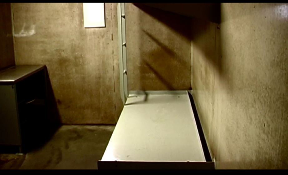 A photo of a bed and desk in a cell at Northern Correctional Institution in Somers, Connecticut. A metal cot-like bed is against a concrete wall on the right. On the left, a small desk and door. The space is small, barren, concrete.