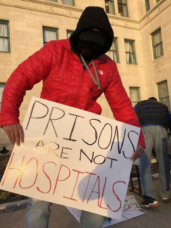"""A person in a red coat, black facemask, and black hood holds a sign that says """"Prisons are not hospitals"""" in front of the Connecticut State Capitol building in December 2020."""
