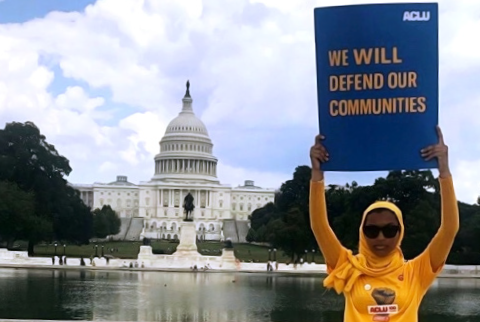 "Rowanne Mustafa poses with ""We will defend our communities"" ACLU poster outside of the U.S. Capitol Building"