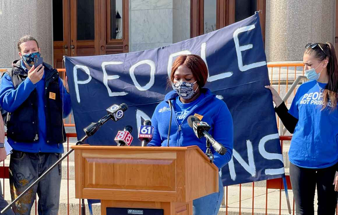 Smart Justice leader shelby Henderson, in a blue Smart Justice zip up and mask, speaks at a podium in front of the CT state capitol. Behind her is a blue people not prisons banner held by two other Smart Justice leaders.