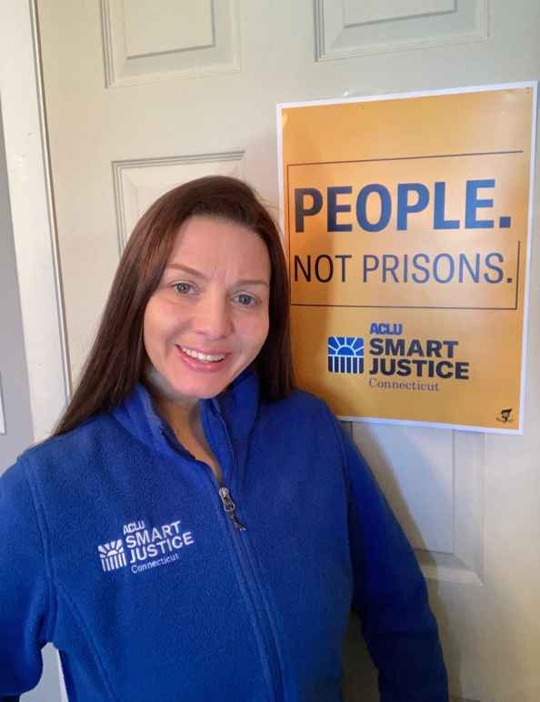 "ACLU-CT Smart Justice leader Tracie Bernardi stands in front of a yellow Smart Justice ""People Not Prisons"" poster. She is wearing a blue ACLU of Connecticut Smart Justice zip up sweatshirt, standing, and smiling."