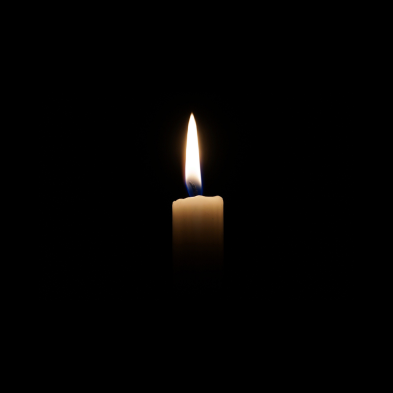 a white candle, lit, is in the center of the frame. The rest of the image is a black square