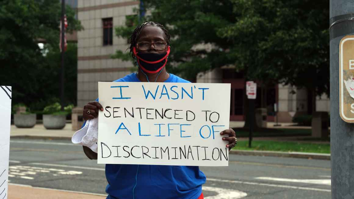 ACLU-CT Smart Justice leader stands with sign: I wasn't sentenced to a life of discrimination