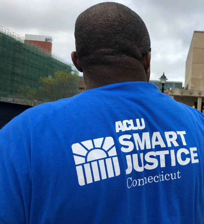 From behind, a man stands in a blue ACLU of Connecticut Smart Justice shirt