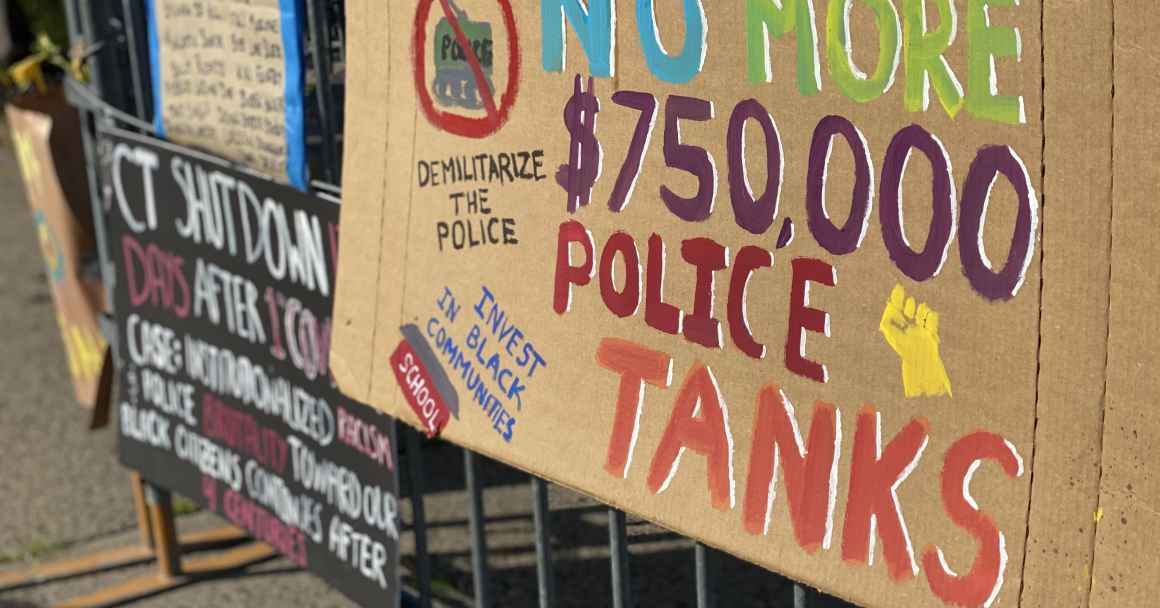 "A cardboard sign taped to a fence outside of a Stamford Connecticut protest. The sign says: ""No more $750,000 police tanks,"" ""demilitarize the police,"" and ""invest in our communities."" It has a drawing of a raised fist, and of a tank crossed out."