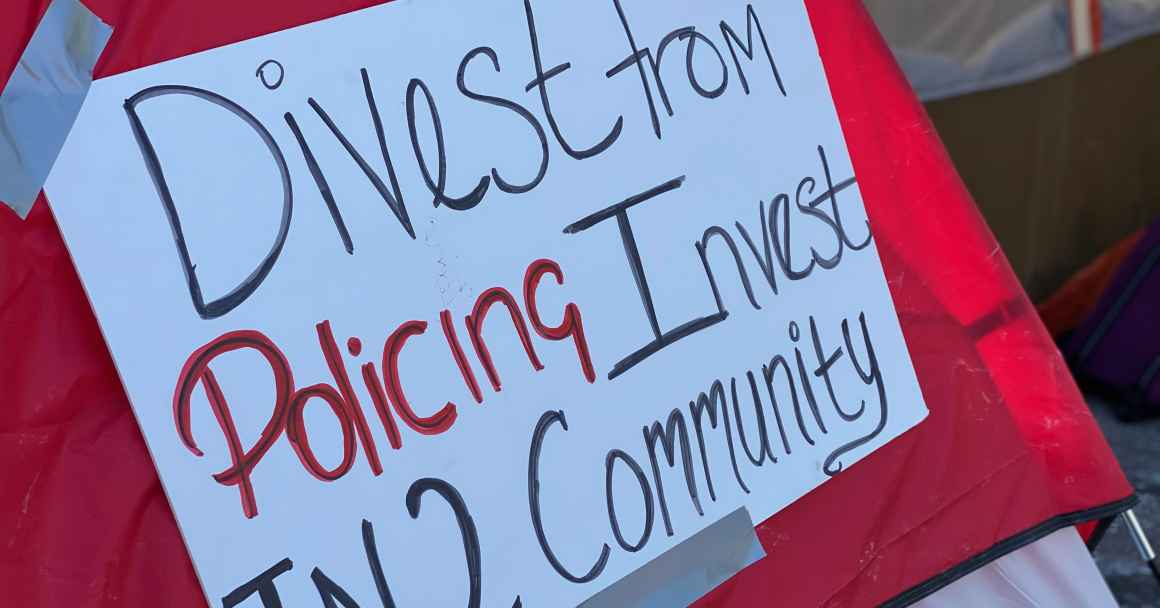 Red tent with white sign. Sign reads: Divest from policing / invest in2 community