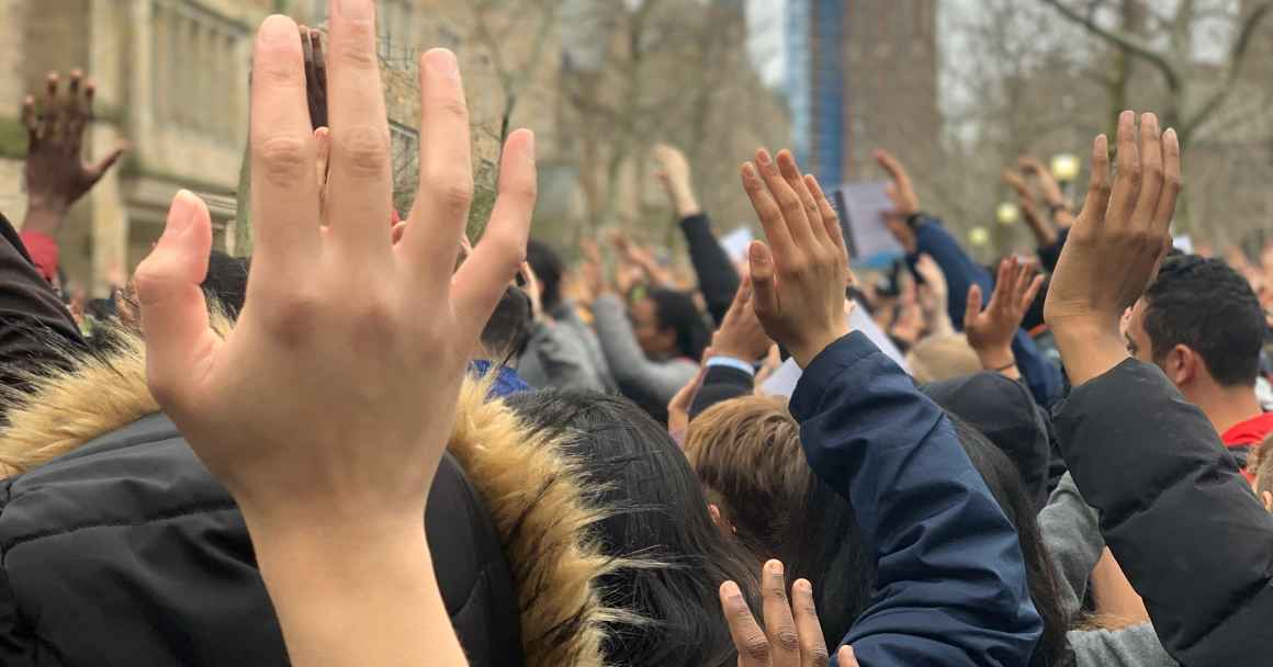 Photo of people with hands raised.